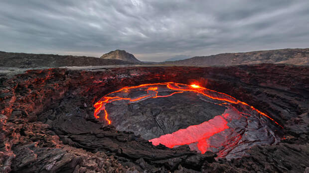 Эрта Але Эфиопия Это самое неподходящее для существования человека место на нашей планете. Когда садиться солнце, дым начинает выходить из трещин под вашими ногами, а жуткое, кроваво-красное свечение исходит из лавовых озер, которых здесь насчитывается целых пять штук. Температура воздуха достигает 55 градусов по Цельсию: отправиться сюда может отважится лишь самый храбрый путешественник.