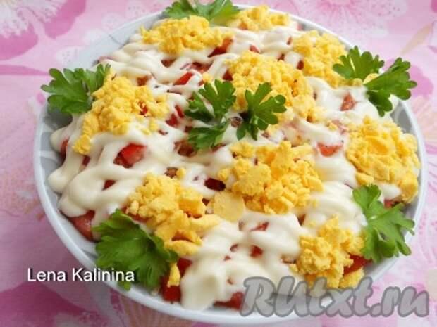 Нанести сверху сеточку из майонеза. Украсить этот замечательный и вкусный слоеный салат с помидорами тертыми желтками и зеленью.