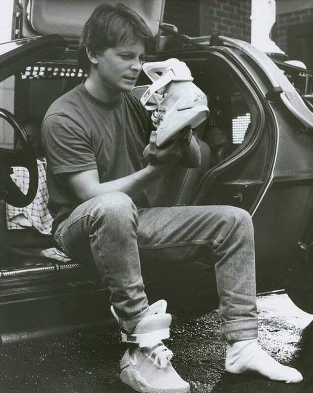 """Майкл Дж. Фокс рассматривает кроссовки """"из будущего"""" Nike MAG на съемках фильма """"Назад в будущее 2"""", 1989 год. история, ретро, фото, это интересно"""