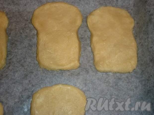 Через 30 минут достаём тесто и раскатываем его в пласт толщиной 0,5-1 см. С помощью формочки или бумажного трафарета вырезаем печенье в виде пасхи. Кладём печенье на противень, застеленный бумагой для выпечки, и отправляем в разогретую до 180 градусов духовку на 15-20 минут.