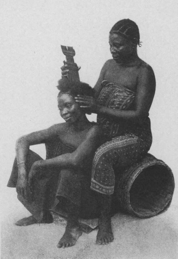 Восточноафриканские женщины заплетают друг другу волосы.