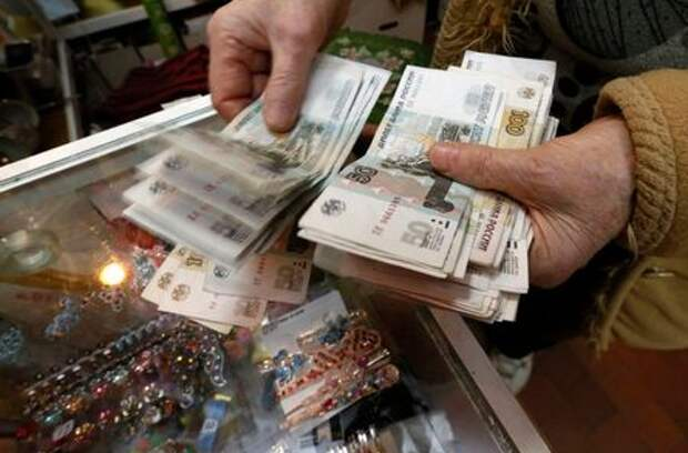 A vendor counts Russian rouble banknotes earned during the day at a home appliances shop in the Siberian city of Krasnoyarsk, Russia, January 11, 2016. Russia's rouble fell further on January 20, setting a new record low of over 81 roubles per dollar as a bearish mood gripped Russian financial markets. Picture taken January 11, 2016. REUTERS/Ilya Naymushin