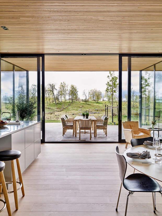 Современная шведская дача со стеклянными стенами, окруженная со всех сторон зелёными лугами