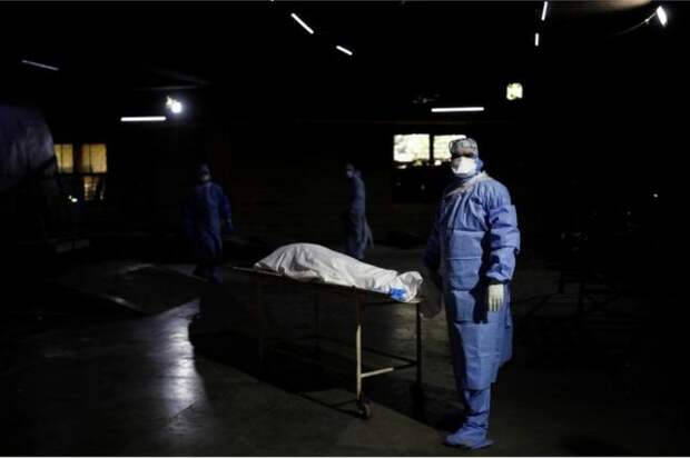 A health worker wearing personal protective equipment (PPE) stands next to the body of a man, who died from the coronavirus disease (COVID-19), before his cremation, at a crematorium in New Delhi, India April 21, 2021.