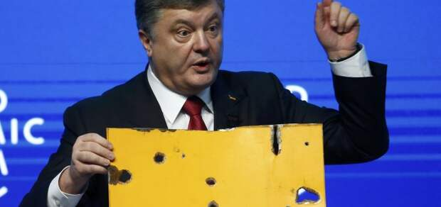 Ukrainian President Poroshenko holds a fragment of a bus body which he says shows a Russian missile attack on a civilian bus as he addresses The Future of Ukraine event in the Swiss mountain resort of Davos