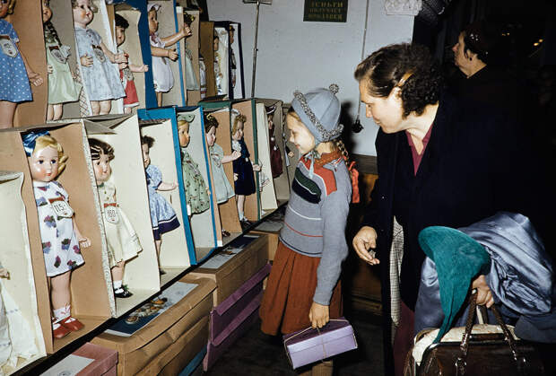 Russia, woman and girl looking at dolls for sale at store in Moscow