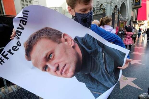 A protester wearing a face mask holds a poster of Alexei Navalny in Hollywood during a demonstration in support of the Russian opposition leader, who was sentenced to jail, in Los Angeles, California, U.S. February 6, 2021. REUTERS/Ringo Chiu