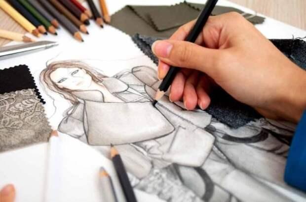 девушка рисует черным карандашом плащ