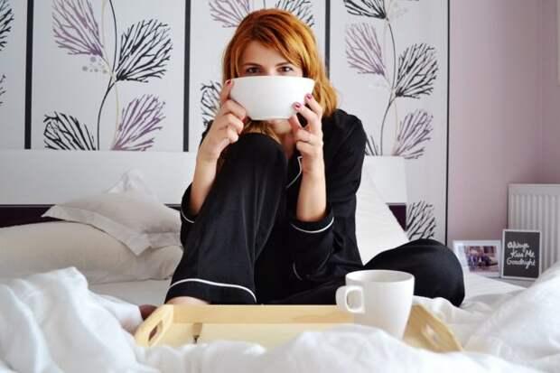 рыжая девушка в пижаме на кровати с чашкой в руках