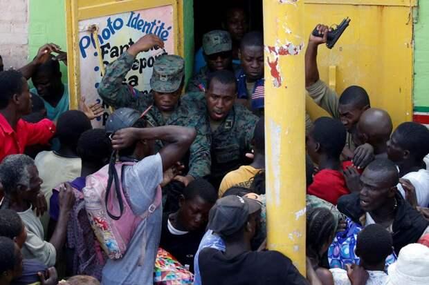 Солдаты стреляют в воздух в попытке навести порядок в толпе людей, которые ждут раздачи гуманитарной помощи в пострадавшем от урагана «Мэтью» городе Жереми на Гаити.