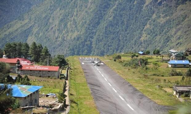 Лукла, Непал Аэропорт имени Тэнцинга и Хиллари Многие альпинисты, решившие покорить Эверест, начинают свой путь к вершине мира из города Лукла. Местный аэропорт имени Тэнцинга и Хиллари будто был создан для таких вот искателей приключений, чтобы проверить серьезность их намерений и стойкость. Воздушная гавань расположена на высоте 2900 метров над уровнем моря. Взлетно-посадочная полоса окружена вершинами и заканчивается обрывом. И без того непростую обстановку взлета и посадки усложняют скапливающиеся вокруг облака.
