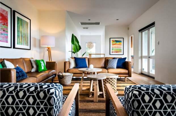 Черно-белые орнаменты на обивке кресел и обшивке подушек в просторной гостиной частного дома