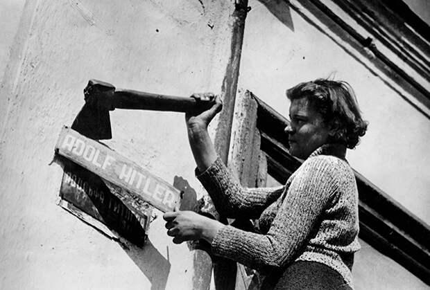 Женщина снимает табличку с надписью «Адольф Гитлер». Конец Второй мировой воны