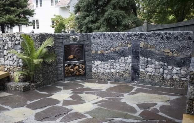 Декоративная ограда из габионов, заполненная разноцветными камнями.