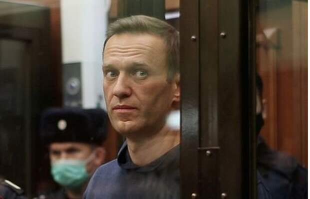 A still image taken from video footage shows Russian opposition leader Alexei Navalny, who is accused of flouting the terms of a suspended sentence for embezzlement, inside a defendant dock during the announcement of a court verdict in Moscow, Russia February 2, 2021. Press service of Simonovsky District Court/Handout via REUTERS