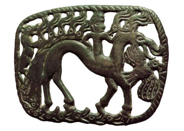 Богиня на коне-лосе. Вверху семь лосиных голов, зверь и птица – символы животного мира, которым правит богиня. Замыкает композицию ребристая линия, знак воды окружающей землю.
