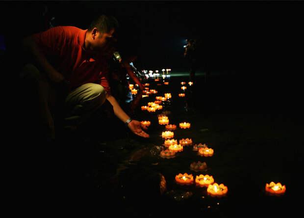 Накануне фестиваля Дуань-у 7 июня 2008 года в Пекине китайцы пускают свечи по реке в память о жертвах землетрясения 12 мая в провинции Сычуань.  Во время землетрясения, самого сильного в Китае за последние три десятилетия, погибло более 69 тысяч, миллионы людей потеряли кров. (Photo by Guang Niu/Getty Images)