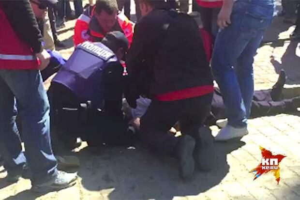 Пожилой человек простоял с цветами около 8 часов и упал. Полицейские и медики пытаются оказать ему первую помощь. Не помогло... Фото: Владимир ВОЛОШИН