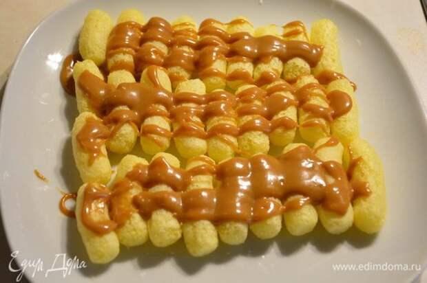 Сложите кукурузные палочки рядами. Сверху полить карамелью.