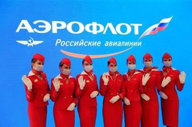 Participants wearing protective face masks pose for a picture at the stand of Aeroflot airlines during the St. Petersburg International Economic Forum (SPIEF) in Saint Petersburg, Russia, June 4, 2021. REUTERS/Evgenia Novozhenina