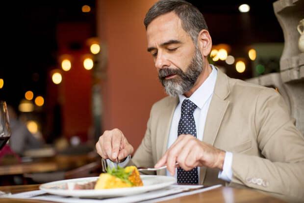 бородатый мужчина в костюме ест в ресторане