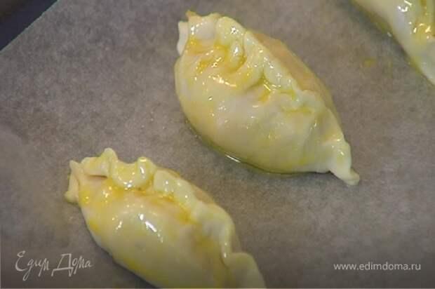Противень выстелить бумагой для выпечки, смазать ее оливковым маслом, выложить пирожки и выпекать в разогретой духовке 20 минут.