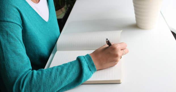Женщина сидит за столом и пишет
