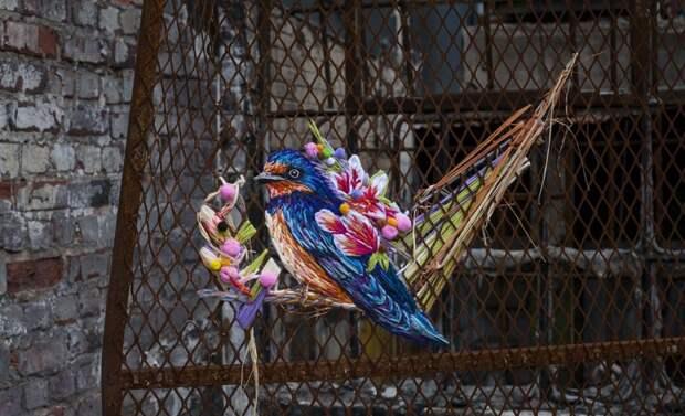 Вышитая на заборе птичка