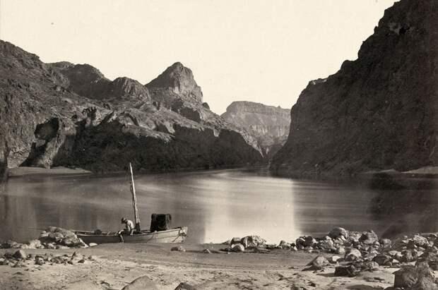 Человек в деревянной лодке на ерегу реки Колорадо в Черном Каньоне, Мохаве Каунти, штат Аризона. Снято в 1871 году