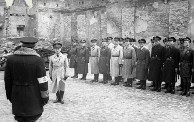 Глава еврейской полиции Варшавского гетто Юзеф Шеринский принимает доклад начальника одного из отрядов Якуба Лейкина. Шеринского позже поймали на воровстве и Лейкин занял его место.