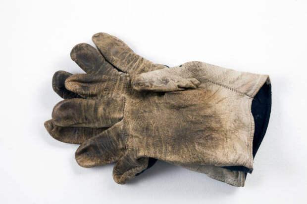 an old and very dirty work glove lies on a white background - грязная перчатка стоковые фото и изображения