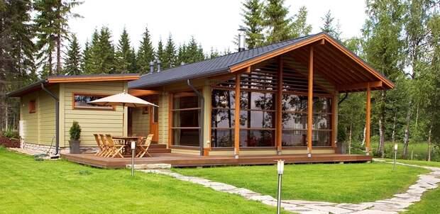 Дача из дерева с большой террасой и светлой гостиной.