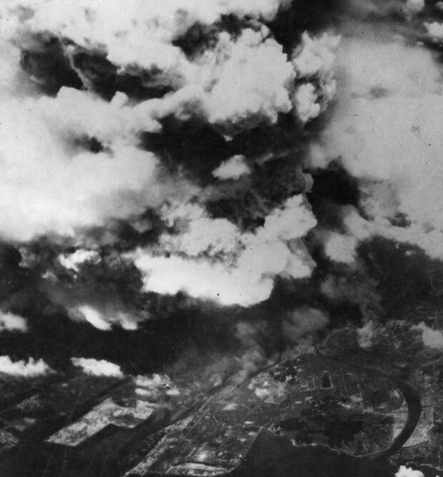 7. Фото, сделанное из одного из двух американских бомбардировщиков 509-ой сводной группы, вскоре после 8:15, 5 августа 1945 года, показывает поднимающийся от взрыва дым над городом Хиросима. К моменту съемки уже произошла вспышка света и жара от огненного шара диаметром 370 м, и взрывная волна быстро рассеивалась, уже причинив основной вред зданиям и людям в радиусе 3,2 км. (U.S. National Archives)