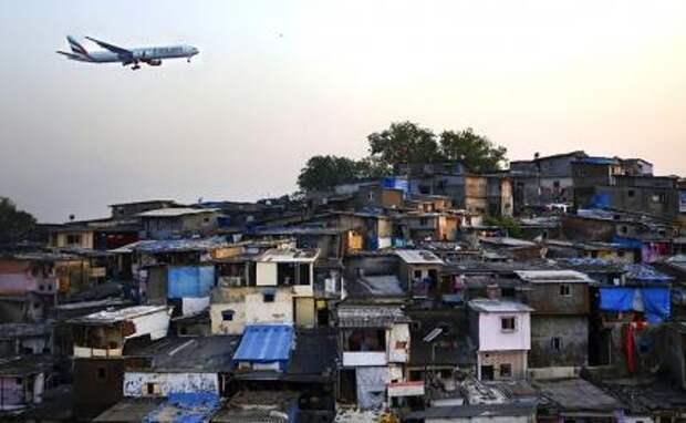 На фото: самолет пролетает над трущобами возле международного аэропорта имени Чатрапати Шиваджи в Мумбаи, Индия.